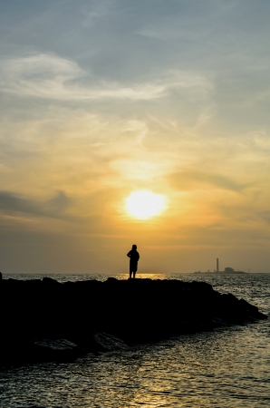 Sunset with lonely woman in Thai beach photo