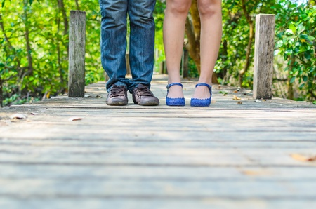 Lover feet standing on the wood bridge in Thailand Stock Photo