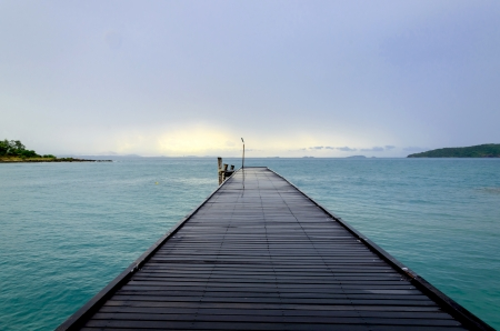 Wood bridge to the sea in Thailand photo