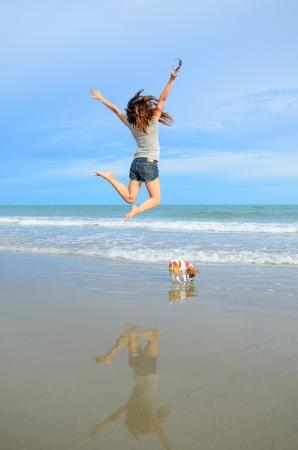 Salto da mulher nova com seu filhote de cachorro bonito jack russel na praia, na Tail