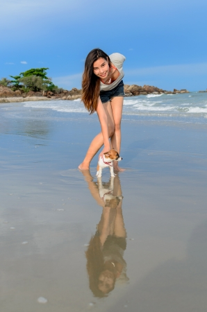 Young woman with her cute jack russel puppy on the beach, Thailand photo