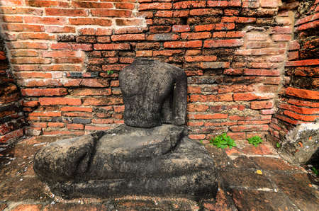 Ancient Buddha sculpture with the wall brick background in Sukothai historical park, Thailand photo