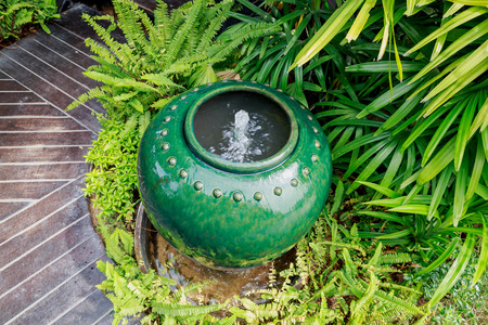 overflow: Jar fountain in with overflow water,Thailand