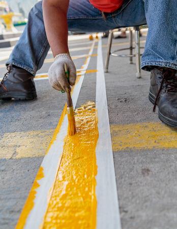 L'homme est la peinture la ligne jaune sur la route en béton Banque d'images - 25664300