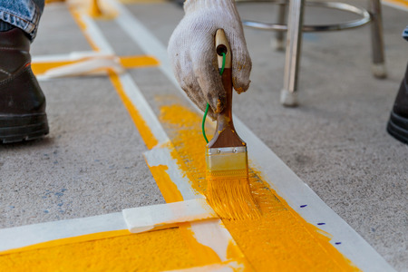 The man is painting the the yellow line on the concrete road Stock Photo