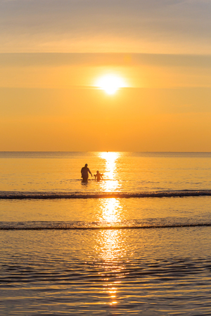 Happy family walking on the beach at sunset, east of Thailand