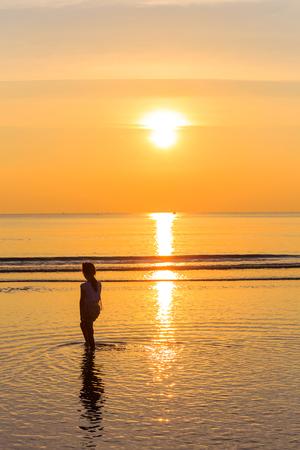 Silhouette fille solitaire sur la plage au coucher du soleil, à l'est de la Thaïlande Banque d'images - 25664450