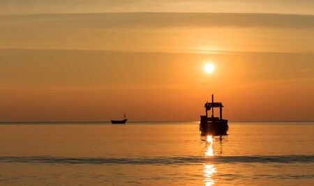 Silhouette boat on the sea with sunset