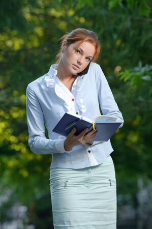 Woman with notebook talking on the phone in the park Stock Photo - 10994946