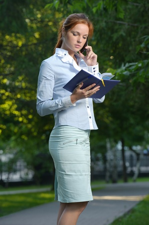 Woman with notebook talking on the phone in the park Stock Photo - 10994948