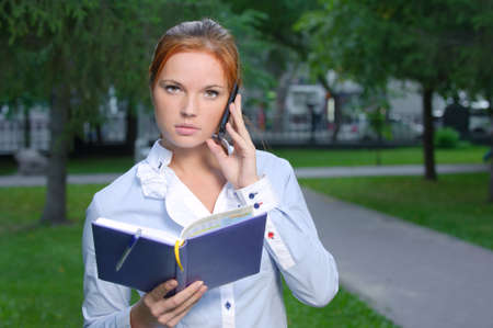 Woman with notebook talking on the phone in the park Stock Photo - 10994945