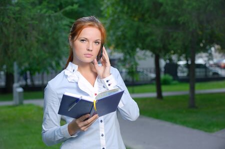 Woman with notebook talking on the phone in the park Stock Photo - 10994947