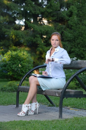 Girl with notebook sitting on the bench looking over the clock