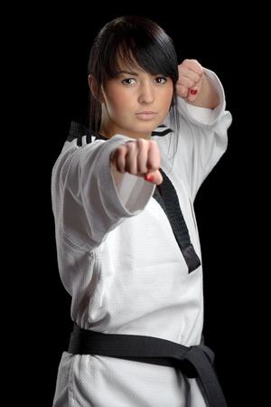 Taekwondo. Mujer en un kimono aislados sobre el fondo negro photo