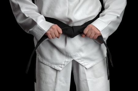 Woman in a kimono and belt for martial arts on black background