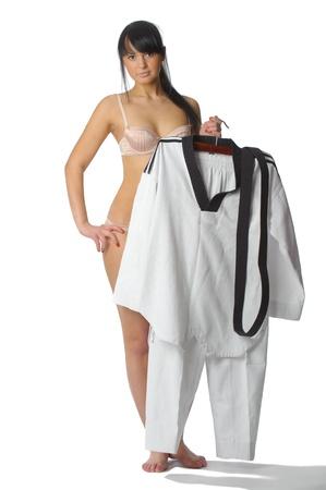 jujitsu: Taekwondo female fighter with kimono in left hand on white background Stock Photo
