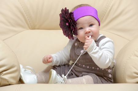 Portrait of toddler on chair gnawing a lace with flower dressing on head Stock Photo