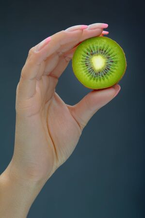 Hand holding kiwi on blue Stock Photo