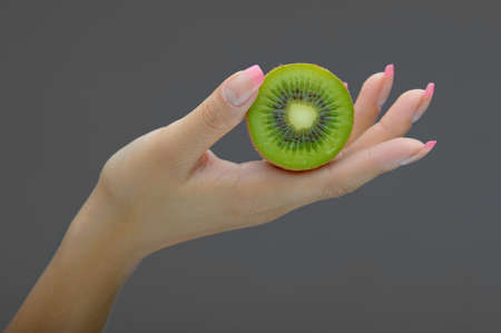 Hand holding kiwi isolated on white Stock Photo