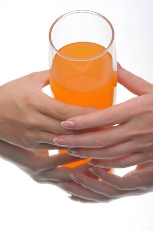 Two hands holding glass of orange fluid on white Stock Photo