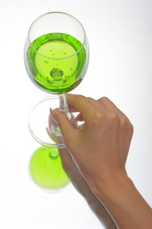 Hand holding glass of green fluid on white