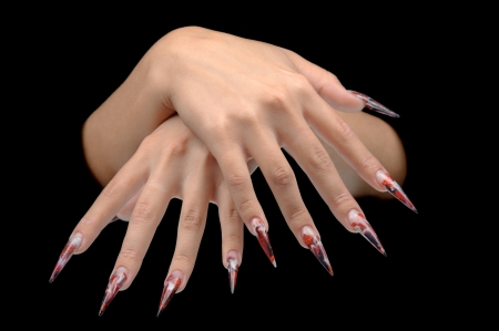 nailart: Closeup of hand of young woman long nail-art manicure on nails isolated on black