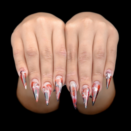 Closeup of hand of young woman long nail-art manicure on nails isolated on black photo