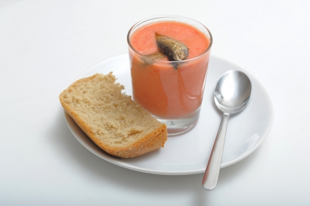 Served homemade gazpacho with sprats in the cup with spoon and bread on the white plate