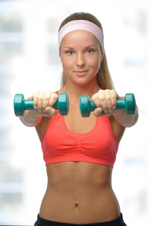 Image of blonde smiling woman with barbell in hand over white Stock Photo