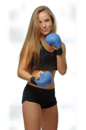 Young blonde woman with boxing gloves over white