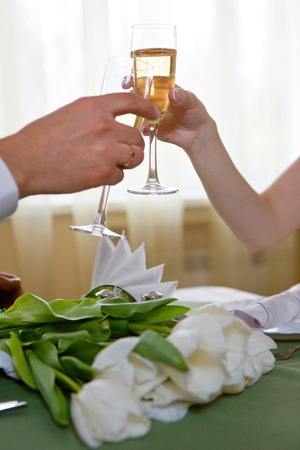 Glasses of champagne in the hands of lovers to newlyweds lumen closeup