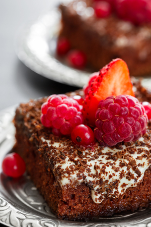 condensed: A piece of chocolate cake with cream lies on a plate decorated with berries. Stock Photo