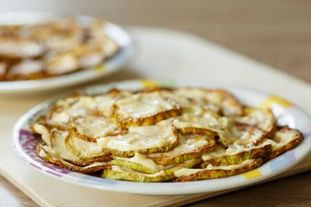 Zucchini chopped and fried slices with mayonnaise on a plate. There is space for text