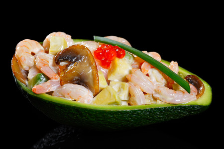 Salad with shrimps, avocado, mushrooms and red on a black background