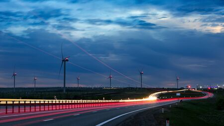 Wind generators, trassers, lights, twilight Foto de archivo