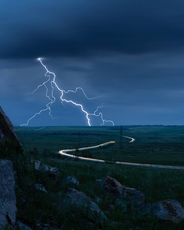 An evening thunderstorm, lightning sparkles, cars rush, tracers are visible
