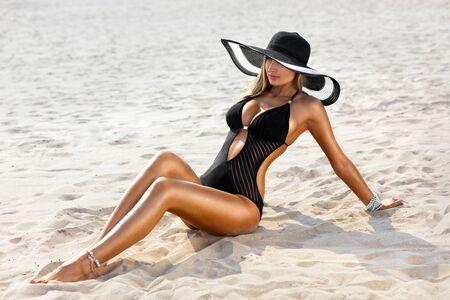 traje de bano: foto de una mujer joven sentada en la playa