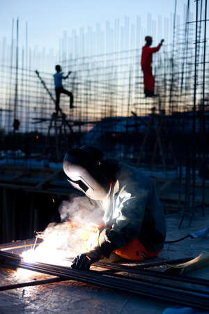erecting: Welder does the job Workers erecting steel in the background Stock Photo