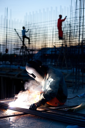 erecting: Welder does the job.Workers erecting steel in the background