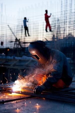 soldadura: Soldador hace el acero erigir job.Workers en el fondo