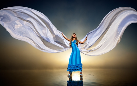 woman standing at the water surface in a blue dress  it makes the wings flap of tissue Фото со стока