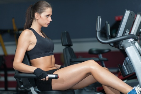 body conscious: Sportive woman doing exirsise on cycling simulator in the sport club