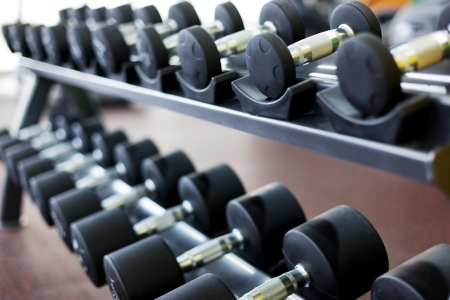 staying: many dumbbells are on stand at the gym