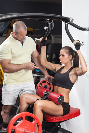 Woman at the health club with her personal trainer, learning the correct form on the pulldown machine  photo