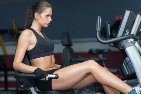 Sportive woman doing exirsise on cycling simulator in the sport club photo