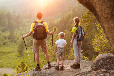 Dad with two children looking at sunrise above forest