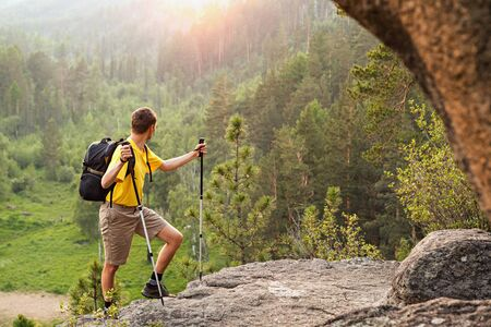 Man with small backpack go up mountain and looking at sunrise photo