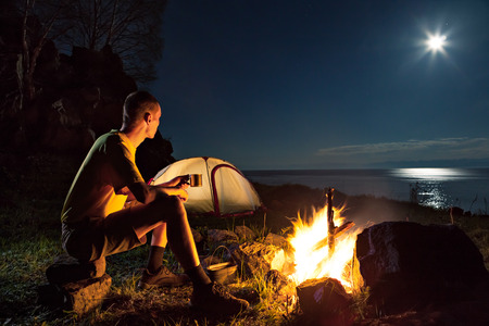 Hiking tourist have a rest in his camp at night near campfire photo