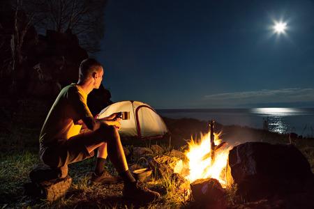 Wandelen toeristische hebben een rust in zijn kamp bij nacht dichtbij kampvuur