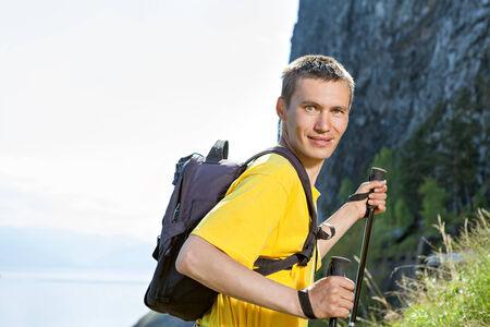 go up: Cheerful man with small backpack go up mountain Stock Photo